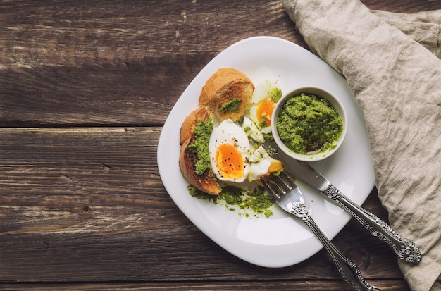 Boiled egg with toasted bread and pesto sauce on rustic wooden background. top view.