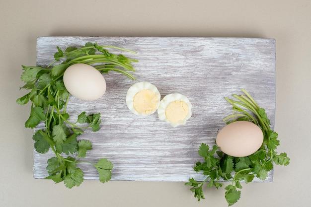 나무 커팅 보드에 삶은 계란과 삶은 계란.