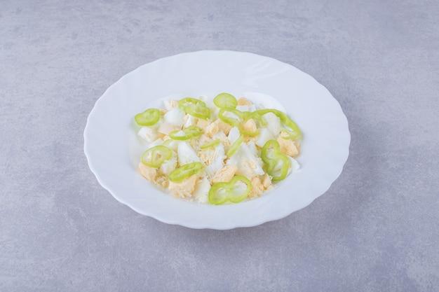 Вареные яйца и дольки перца в белой тарелке.