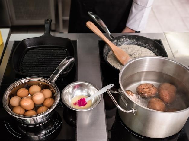Вареные яйца и картофель - ингредиенты для вкусной еды. процесс приготовления на профессиональной кухне