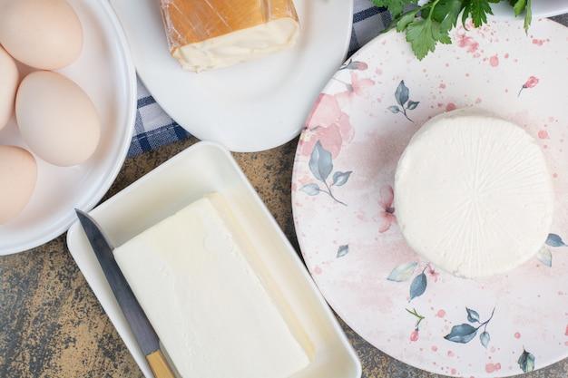 Вареные яйца и различные сыры на тарелках.