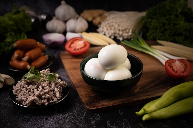 Boiled eggs in a black bowl, garlic, sausage, tomatoes placed on a wooden cutting board