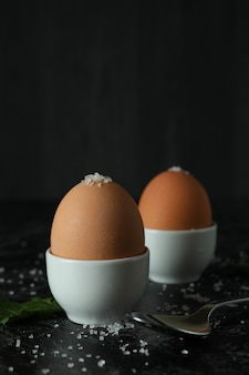 Boiled eggs on black smokey table, close up