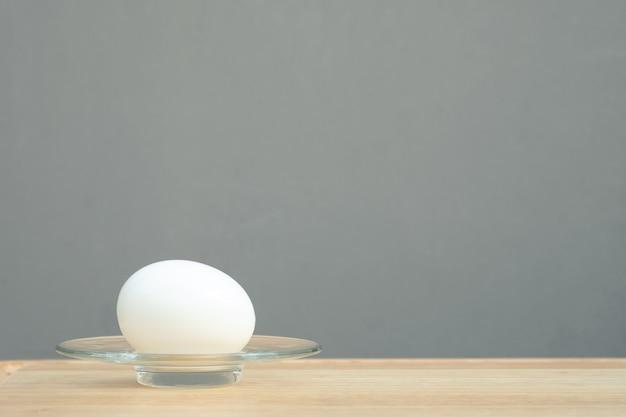 ゆで卵。木製のテーブルの上のプレートでゆで卵。