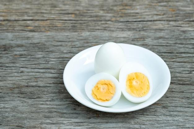 ゆで卵。木製のテーブルの上の白いセラミックプレートでゆで卵。