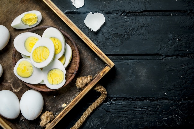 Boiled eggs in bowl. on a black rustic background.