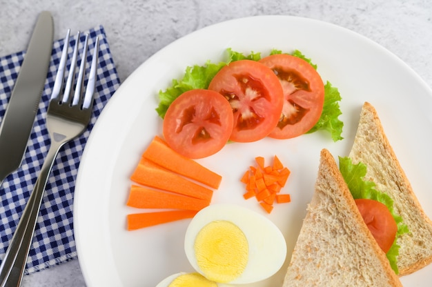 Boiled eggs, bread, carrots, and tomatoes on a white plate with a knife and fork.