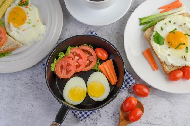 ゆで卵、にんじん、トマト、フライパンにトマト、木のスプーン。