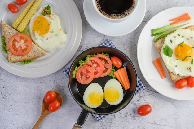 Boiled eggs, carrots, and tomatoes on a pan with tomato on a wooden spoon and coffee cup.