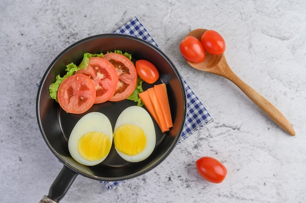 Boiled eggs, carrots, and tomatoes on a pan with tomato on a wooden spoon.