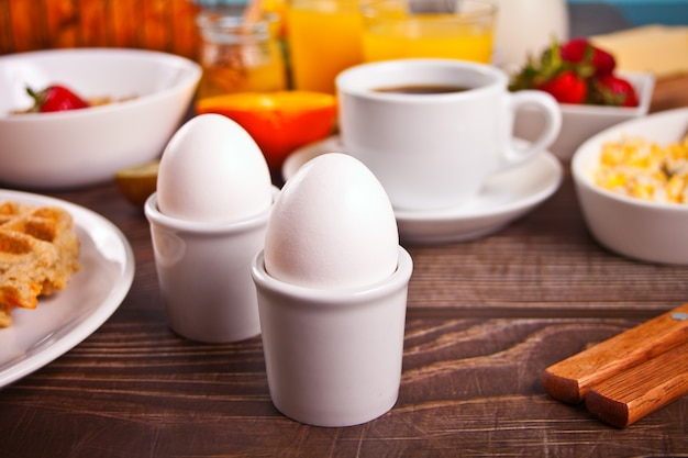 Boiled eggs, cup of coffee, juice,fruits, toasts on the wooden table
