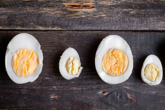 Boiled eggs cut in a half on a dark wooden background. top view.