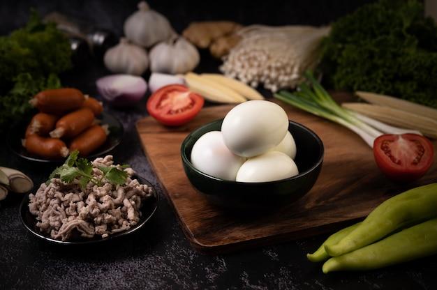 木製のまな板の上に置いた黒いボウル、ニンニク、ソーセージ、トマトのゆで卵