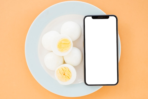 Boiled eggs and mobile phone with white screen display smartphone on ceramic white plate