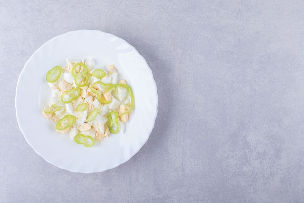 Uova sode e fette di pepe in piatto bianco.