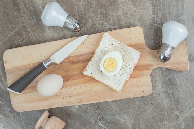 Boiled eggs and toast slice on cutting board with knife and spices. high quality photo