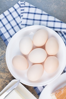 Boiled eggs on white plate with tablecloth.