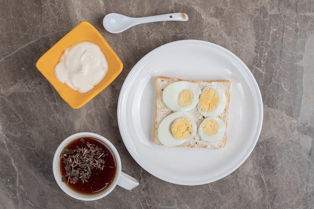 皿にパンとお茶を入れたゆで卵。高品質の写真