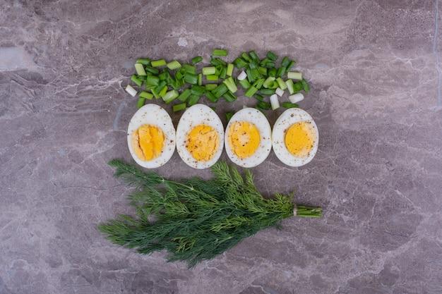 Вареные яйца с нарезанным луком и пучком укропа
