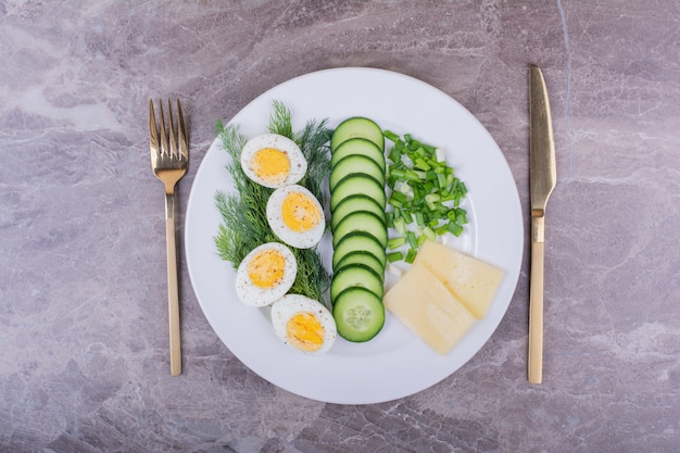 Boiled eggs with green salad in a white plate.