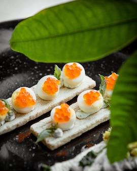 Boiled eggs with orange caviar