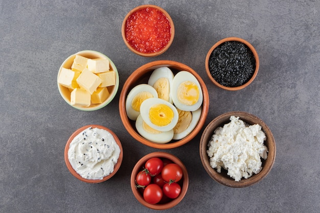 Вареные яйца с красной и черной икрой на камне.