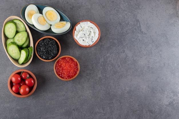 Вареные яйца с сосисками и нарезанными огурцами на каменном фоне.