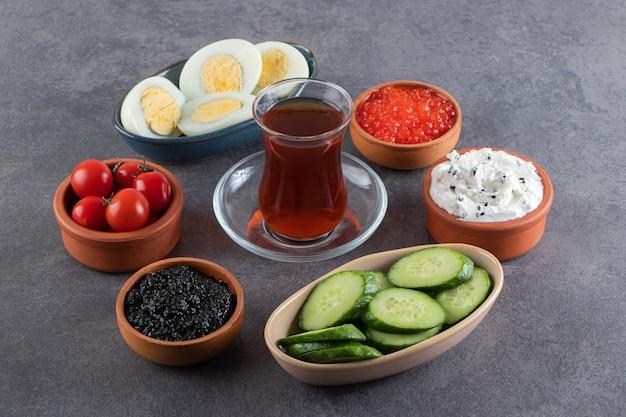 Вареные яйца с сосисками и нарезанными огурцами на каменном столе.