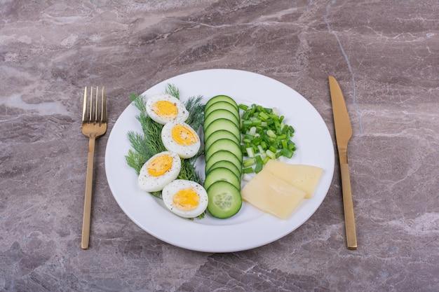 Uova sode con cetrioli a fette ed erbe aromatiche in un piatto bianco.