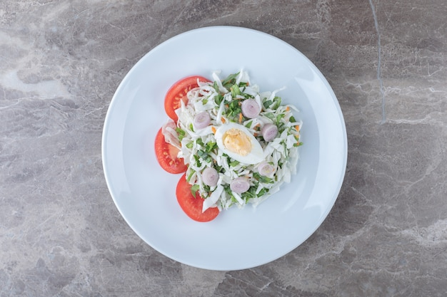 Boiled eggs with vegetable salad on white plate.