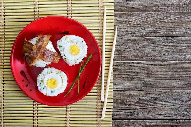 Вареные яйца, завернутые в рис с зеленым луком, с кусочками бекона на красной тарелке. завтрак в азиатском стиле. вид сверху