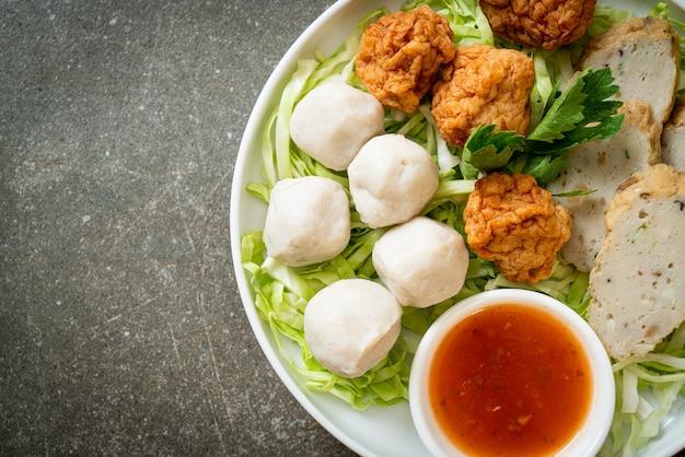 茹でたフィッシュボール、エビのボール、スパイシーなディップソースを添えた中国の魚肉ソーセージ