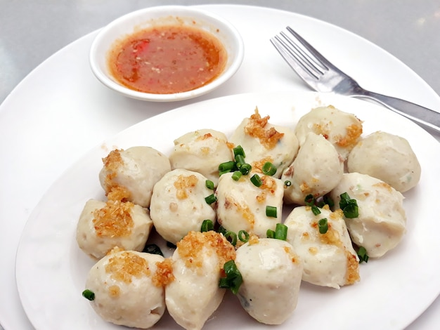 Boiled fish balls in a white plate with a small bowl of spicy fish ball sauce
