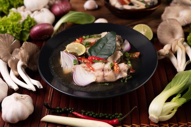 그릇에 토마토, 버섯, 고수풀, 파, 레몬 그라스를 넣은 삶은 생선 주입