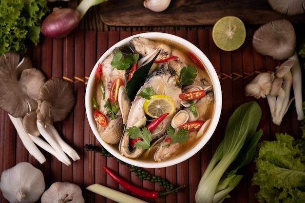 Отвар из отварной рыбы с помидорами, грибами, кориандром, зеленым луком и лемонграссом в миске