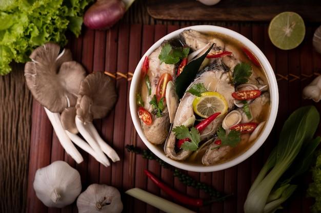 ボウルにトマト、マッシュルーム、コリアンダー、ネギ、レモングラスを入れたゆで魚の注入