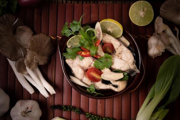 Infuso di pesce bollito con pomodori, funghi, coriandolo, cipollotto e citronella in una ciotola