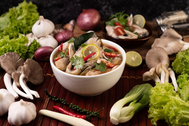 Boiled fish infusion with tomatoes, mushrooms, coriander, spring onion and lemongrass in a bowl