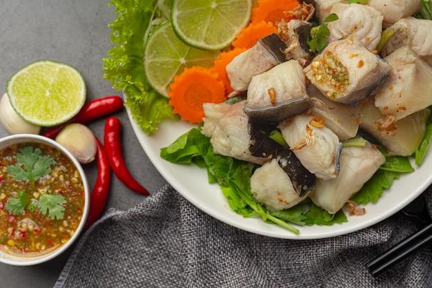 매운 소스와 야채를 곁들인 삶은 생선