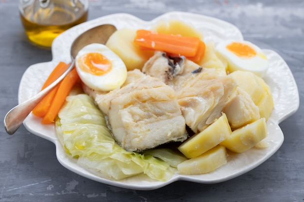 흰 접시에 야채와 삶은 달걀과 삶은 생선