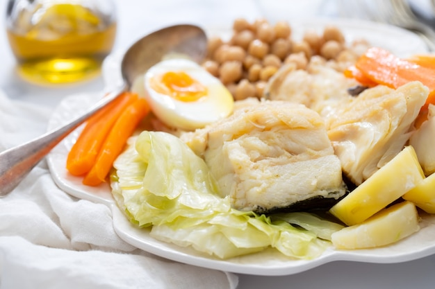 Boiled fish with vegetables and boiled egg on white plate