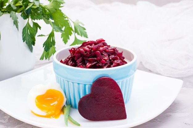 Boiled grated beet  in a bowl, chiken egg and parsley