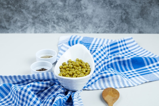 Вареный зеленый горошек в белой миске на белом столе со специями, ложкой и скатертью.