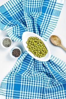 Зеленый горошек отварной в белой миске со специями, ложкой и скатертью.