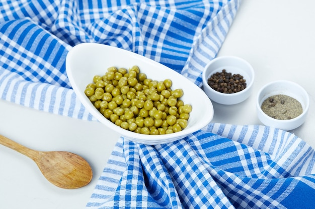Boiled green peas in a white bowl with spices, a spoon, and a tablecloth.
