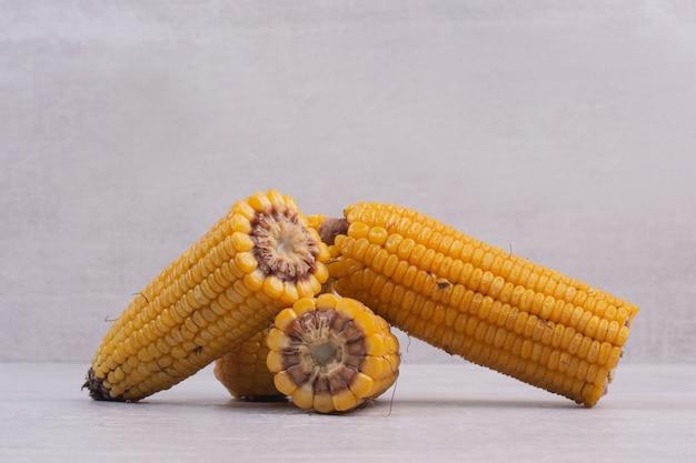 Boiled half cut corns on white table.