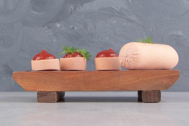 Вареные домашние колбаски и кетчуп на деревянной доске.