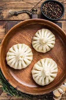 나무 접시에 양고기 양고기를 넣은 삶은 킨칼리 만두. 나무 배경입니다. 평면도.