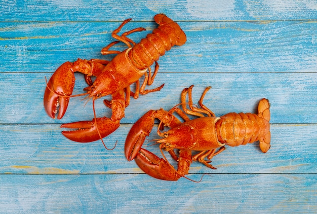 Boiled lobster with tasty seafood served on old wooden table.