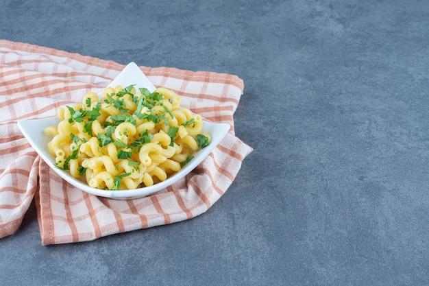 Вареные макароны с зеленью в белой миске.